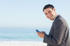 Cheerful businessman sending a text message Royalty Free Stock Photos