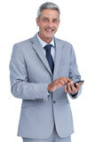 Cheerful businessman sending text message looking at camera Royalty Free Stock Images