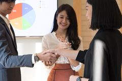 Cheerful businessman shaking hands with businesswoman while businesspeople applauding in the background, Successful business royalty free stock images