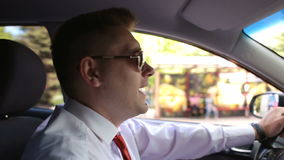 Cheerful businessman sings behind wheel of a car. stock footage