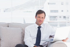 Cheerful businessman sitting on couch Royalty Free Stock Photo