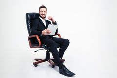 Cheerful  businessman sitting in office chair and using tablet Royalty Free Stock Photography