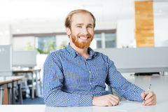 Cheerful businessman sitting at the table and writing. Cheerful attractive bearded businessman sitting at the table and writing Stock Image