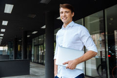 Cheerful businessman standing ang holding laptop Royalty Free Stock Image