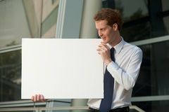 Cheerful Businessman Staring Blank Poster Sign. A cheerful businessman staring at a blank poster sign outside of a glass office building.  Custom text insert Stock Photo