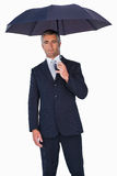 Cheerful businessman in suit under umbrella Stock Photo