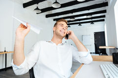Cheerful businessman talking on cell phone and throwing paper plane Royalty Free Stock Photography