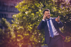 Cheerful businessman talking on mobile phone against tree Stock Photos