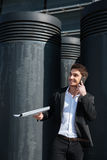 Cheerful businessman talking on phone. Handsome businessman talking on phone in the street Stock Image