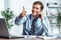 Cheerful businessman talking on the phone and showing thumb up. Photo of successful man working in the office. Business concept royalty free stock image