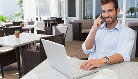 Cheerful businessman talking on phone using his laptop. In patio of restaurant Stock Photography