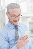 Cheerful businessman text messaging Royalty Free Stock Photography