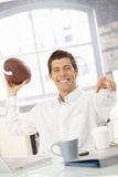 Cheerful businessman throwing football stock images