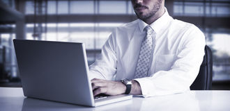 Cheerful businessman using laptop at desk Royalty Free Stock Photo