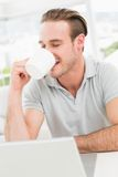 Cheerful businessman using laptop while drinking Stock Photo