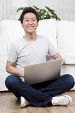 Cheerful businessman using a laptop on the floor Royalty Free Stock Photography