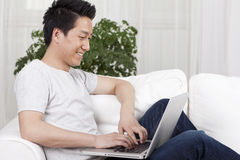Cheerful businessman using a laptop in sofa Royalty Free Stock Photography