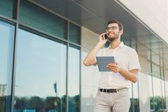 Cheerful businessman using phone and tablet outdoors Stock Images