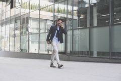 Businessman walking on street and holding iPod. Space f. Cheerful businessman walking on street and holding iPod. Space for copy Stock Photos