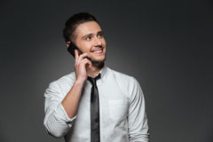 Cheerful businessman in white shirt talking on mobile phone Royalty Free Stock Photo