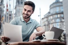 Cheerful businessman working with documents in cafe Stock Photos