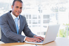 Cheerful businessman working on his laptop Stock Image