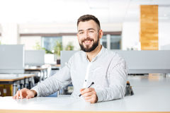 Cheerful businessman working and writing in office Royalty Free Stock Photography