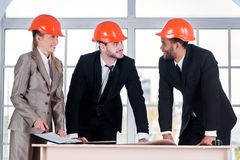Cheerful businessmen architects. Three businessmеn architect me Stock Images