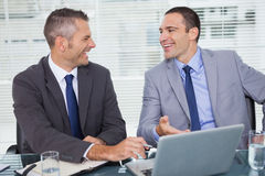 Cheerful businessmen laughing while working Royalty Free Stock Photos