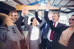 Cheerful businesspeople raising hands stock photo