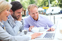 Cheerful businesspeople using laptop together at sidewalk cafe Royalty Free Stock Image