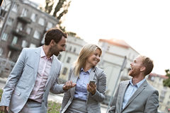 Cheerful businesspeople walking in city Stock Photos