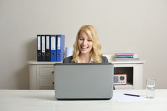 Cheerful businesswoman. Cheerful blonde businesswoman at the office behind her laptop Royalty Free Stock Image