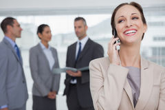 Cheerful businesswoman calling while colleagues talking together Stock Images