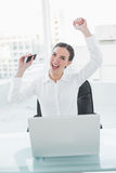 Cheerful businesswoman cheering at office desk Stock Photography