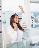 Cheerful businesswoman cheering in office Stock Images