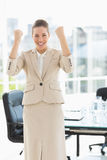 Cheerful businesswoman clenching fists in office Royalty Free Stock Images