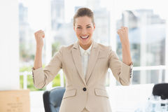 Cheerful businesswoman clenching fists in office Royalty Free Stock Photos