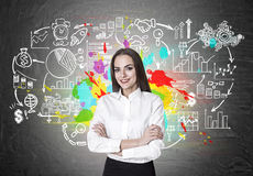 Cheerful businesswoman with crossed hands is standing near a blackboard with start up icons. Stock Image
