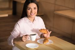 Businesswoman drinking coffee with croissants stock photo