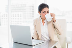 Cheerful businesswoman drinking from mug while working on laptop Royalty Free Stock Image