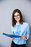 Cheerful businesswoman with folders over gray background Royalty Free Stock Photography