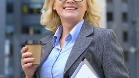 Cheerful businesswoman having coffee break at work, caffeine addiction, closeup. Stock footage stock footage