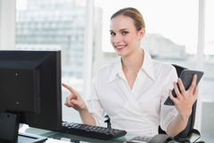 Cheerful businesswoman holding calculator sitting at desk looking at camera Royalty Free Stock Photo