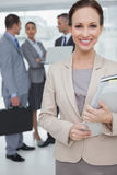 Cheerful businesswoman holding files posing Stock Photos