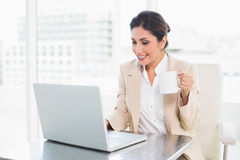 Cheerful businesswoman holding mug while working on laptop Stock Photo