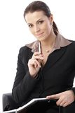 Cheerful businesswoman holding pen Stock Photo