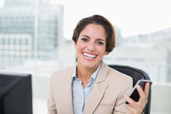 Cheerful businesswoman holding smartphone Stock Image