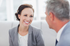 Cheerful businesswoman listening to her workmate talking stock photo