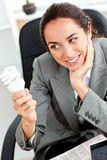 Cheerful businesswoman looking at a light bulb Royalty Free Stock Photo